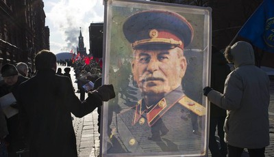 Communist supporters carry a portrait depicting Soviet dictator Josef Stalin as they line up to place flowers on Stalin