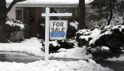 In this Wednesday, Feb. 27, 2013 photo, a for sale sign hangs outside a home in Glenview, Ill. Average U.S. rates on fixed mortgages were little changed the first week of March, hoverin