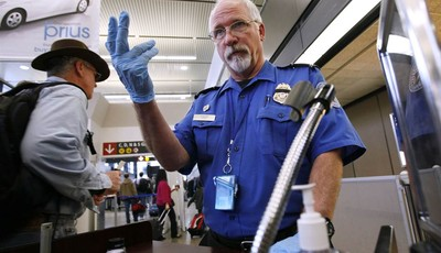 FILE - In this Jan. 4, 2010 file photo, TSA officer Robert Howard signals an airline passenger forward at a security check-point at Seattle-Tacoma International Airport in SeaTac, Wash.