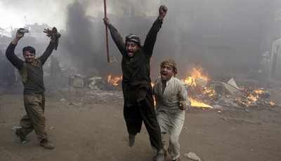 Pakistani men, part of an angry mob, react after burning belongings of Christian families, in Lahore, Pakistan, Saturday, March 9, 2013. A mob of hundreds of people in the eastern Pakis