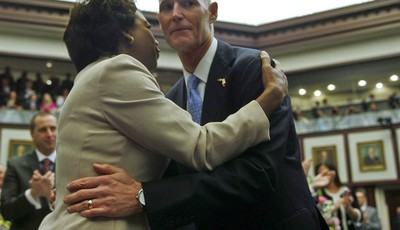 In this Tuesday, March 5, 2013 file photo, Florida Lt. Gov. Jennifer Carroll and Gov. Rick Scott embrace prior to his State of the State speech in the Florida House of Representatives i