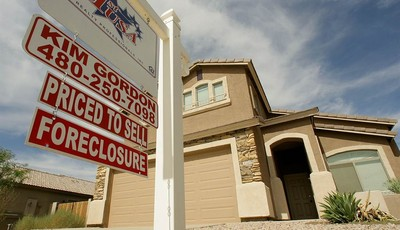 FILE - In this Sept. 26, 2007 file photo, a realty sign stands in front of one of the many homes that are in foreclosure in the Villages of Queen Creek in Queen Creek, Ariz. The number