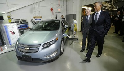 President Barack Obama and Joint Center for Energy Storage Research Director Dr. George Crabtree walk past a hybrid Chevy Volt vehicle used for testing during the president