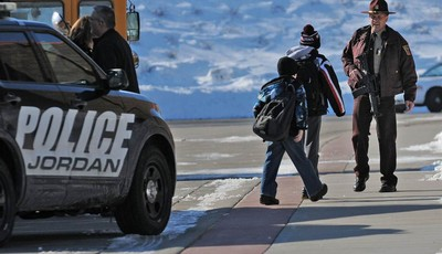 A Minnesota State Patrol officer escorts students into New Prague Middle School in New Prague, Minn., Wednesday, March 20, 2013 after  authorities in New Prague responded to a 911 call