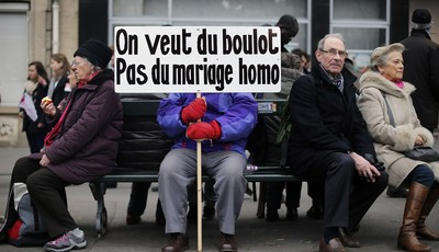 """A protestor holds a placard reading """"We want jobs, not gay marriage"""" during an anti gay marriage and gay adoption demonstration, in Paris, Sunday, March 24, 2013. Thousands of French co"""