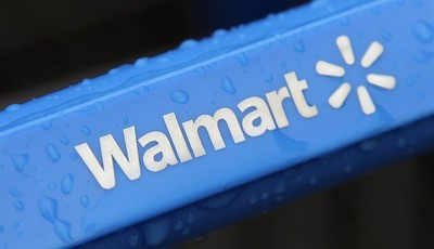 FILE - This Nov. 14, 2011 file photo shows the rain-soaked handle of a shopping cart outside the Walmart store in Mayfield Heights, Ohio. Wal-Mart Stores Inc. will be testing this summe