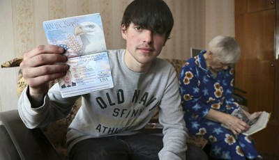 In this photo taken on Saturday, March 20, 2013, Alexander Abnosov shows his American passport to journalists in the Volga river city of Cheboksary, Russia. His 72 -years old grandmothe