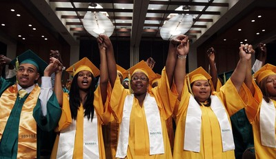FILE - In this May 16, 2011, file photo, graduates sing before President Barack Obama delivers the commencement address at the Booker T. Washington High School graduation at Cook Conven