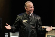 -                Indiana Gov. Mitch Daniels displays his new Purdue leather jacket given to him by the board of trustee after being named as the next president of Purdue University by the school's  trus
