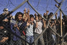 -                FILE - In this Friday, Nov. 5, 2010 file photo shows young immigrants standing behind a fence at a detention center, in the northeastern Greek village of Filakio near the Greek-Turkish