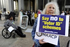 -                Gloria Gilman holds a sign during the NAACP voter ID rally to demonstrate the opposition of Pennsylvania's new voter identification law, Thursday, Sept. 13, 2012, in Philadelphia. Penns