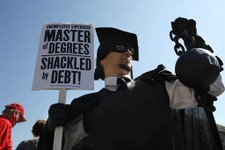 "-                FILE- In this Oct. 6, 2011, file photo, Gan Golan, of Los Angeles, dressed as the ""Master of Degrees,"" holds a ball and chain representing his college loan debt, during Occupy DC activi"