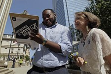 -                In this photo taken Sept. 26, 2012, campaign volunteer Barbara Smalley-McMahan, right, registers 18-year-old Walter Woody III to vote for the first time in Raleigh, N.C. Dozens of volun