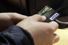 -                FILE - In this May 9, 2012 file photo, a Visa credit card is tendered at opening of the Superdry store in New York's Times Square. Americans boosted their borrowing in August by the lar