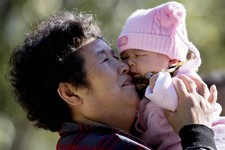 -                A Chinese woman plays with her grandchild at the Ritan Park in Beijing Wednesday, Oct. 31, 2012. A government think tank says China should start phasing out its one-child policy immedia