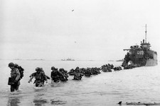 -                FILE - U.S. reinforcements wade through the surf from a landing craft in the days following D-Day and the Allied invasion of Nazi-occupied France at Normandy in June 1944 during World W
