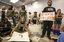 -                Environmentalists Cody Riechers, sitting left,  and Connor Chicott, middle, hold up signs, during a California Coastal Commission meeting in Santa Monica, Calif. Wednesday, Nov. 14, 201