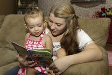 -                In this Monday, Sept. 10, 2012 photo, Kali Gonzalez reads to her daughter Kiah, 2, at their home in St. Augustine, Fla. A new report by the National Women's Law Center says offering pre