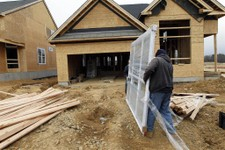 -                In this Feb. 8, 2012 photo, two workers carry a window for a home  under construction in a new subdivision by Toll Brothers, in Yardley, Pa.   Toll Brothers says its fiscal fourth-quart