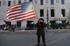 -                Protester Paula Merwin, of Leslie, Mich., stands with an American flag outside the George W. Romney State Building, where Gov. Snyder has an office in Lansing, Mich., Tuesday, Dec. 11,