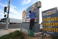-                FILE- In this Friday, Oct. 5, 2012, file photo, Luis Cuevas changes the gas prices at the Shell station off California State Route 99. Forecasters say that ample oil supplies and weak U