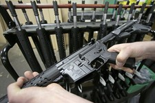-                Veetek Witkowski holds a newly assembled AR-15 rifle at the Stag Arms company in New Britain,  Conn, Wednesday, April 10, 2013. A Connecticut gun-maker announced on Wednesday it intends