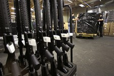 -                A rack of AR-15 rifles stand to be individually packaged as workers move a pallet of rifles for shipment at the Stag Arms company in New Britain, Conn., Wednesday, April 10, 2013. A Con
