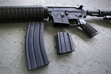-                A 30 round magazine, left, and a 10 round magazine, right, rest below an AR-15 rifle at the Ammunition Storage Component company in New Britain, Conn., Wednesday, April 10, 2013. In the