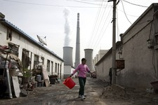 -                A woman walks through a neighborhood near a coal-fired power plant in Beijing on Friday, April 12, 2013. China, the world's largest producer of carbon dioxide, is directly feeling the m