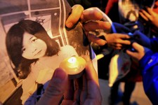-                In this Wednesday, April 17, 2013 photo, Chinese hold pictures of Lu Lingzi, a Boston University graduate student from China who was killed Monday in the Boston Marathon explosions, as