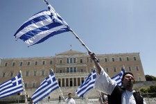 -                A municipal workers dressed in traditional  costume waves a Greek flag outside Greece's Parliament during a protest against government plans to lay off thousands of public sector worker