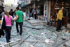-                In this photo released by the Syrian official news agency SANA, Syrians walk on shattered glass from damaged shops at the scene of a powerful explosion which occurred in the central dis