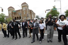 -                Alabama Southern Christian Leadership Conference Director Bishop Calvin Woods, center with bullhorn, leads thousands of young students on a march through downtown Birmingham, Ala., Thur