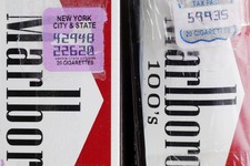 -                In this Tuesday, April 30, 2013 photo, two packs of Marlboro cigarettes, the one on the left with a New York City and state tax stamp, and on the right a Virginia tax stamp, are display