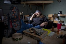 "-                This undated photo provided by A&E, shows Willie Robertson, star of A&E's ""Duck Dynasty,"" at his desk in his office at the Duck Commander warehouse in West Monroe, La. Turning small bus"