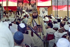 -                In this Thursday, May 2, 2013, an armed supporter of a pro-Taliban religious group Jamiat-e-Ulema Islam (JUI-F), stands guard as others listen the speech of their leader Maulana Shujaul