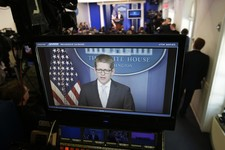 -                White House press secretary Jay Carney, rear, is seen on a television monitor during his daily news briefing at the White House in Washington, Tuesday, May, 14, 2013. Carney touched on