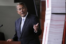 -                House Speaker John Boehner of Ohio gestures toward a stack of paper representing the 20,000 pages of Affordable Health Care Act regulations during a news conference on Capitol Hill in W