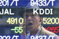 -                A man is reflected on the electronic board of a securities firm in Tokyo Thursday, May 16, 2013. The benchmark Nikkei 225 stock index rose to 15,139.56 early Thursday before falling bac