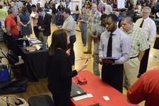 -                In this photo taken Thursday, May 9, 2013, Jennifer Wilhoit of U. S. Express, left, talks with Devin Washington while others wait in line as 63 companies participate in a job fair at th