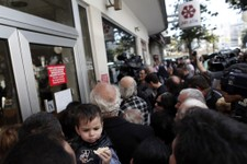 -                FILE - In this Thursday, March 28, 2013 file photo, people wait outside a branch of Laiki Bank in Nicosia. Engineering a financial bailout for Cyprus in March 2013 was such a chaotic pr