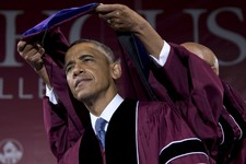 -                President Barack Obama receives an honorary degree from Robert Davidson, Chair of the Board of Trustees, partially visible, during the Morehouse College 129th Commencement ceremony, Sun