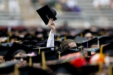 -                A Virginia Tech graduating student holds his cap in the air at Lane Stadium during the 2013 spring graduation ceremony held Friday May 17, 2013 in Blacksburg, Virginia. (AP Photo/The Ro
