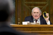 -                Senate Homeland Security and Governmental Affairs Permanent subcommittee on Investigations Chairman Sen. Carl Levin, D-Mich., holds up his own Apple iPhone, on Capitol Hill in Washingto