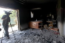 -                FILE - This Sept. 13, 2012 file photo shows a cameraman filming one of  U.S. consulate burnt out offices after an attack that killed four Americans, including Ambassador Chris Stevens o