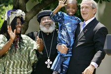 "-                FILE – In is May 30, 2007, file photo President Bush, right, hoists 4-year-old Baron Mosima Loyiso Tantoh, son of Manyongo Mosima ""Kuene"" Tantoh of South Africa, left, who is HIV-positi"