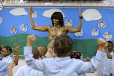 -                First lady Michelle Obama dances with a pre-K class at Savoy Elementary School in Washington, Friday, May 24, 2013. The Savoy School was one of eight schools selected last year for the