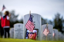 -                A photo of U.S. Marine Lance Cpl. Corey Allen Little leans against his tombstone as volunteers place American flags at the graves of military service members at Georgia National Cemeter
