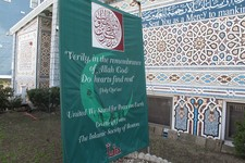 "-                FILE – In this April 19, 2013, file photo a banner reading ""United We Stand For Peace on Earth"" is seen outside the Islamic Society of Boston mosque in Cambridge, Mass. A mosque officia"