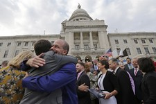 -                FILE - In this May 2, 2013, file photo two men embrace after a gay marriage was signed into law outside the State House in Providence, R.I. Three states and three countries have approve